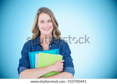Smiling student holding notebook and file against blue background with vignette - stock photo
