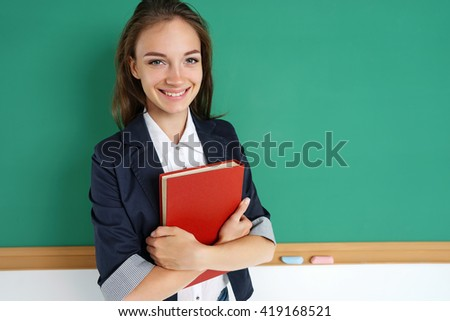 Smiling student hugging books. Photo of teen near blackboard, education concept