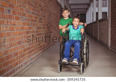Smiling student in a wheelchair and friend beside him on the elementary school grounds - stock photo