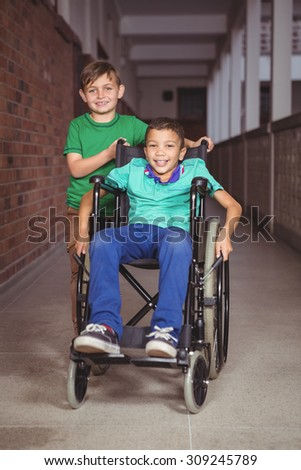 Smiling student in a wheelchair and friend beside him on the elementary school grounds