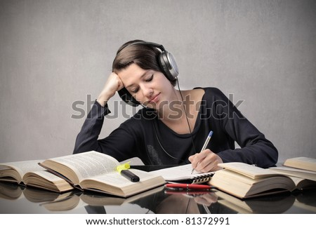 Smiling student listening to music while revising - stock photo