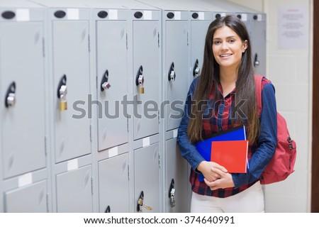 Smiling student posing near locker at university - stock photo