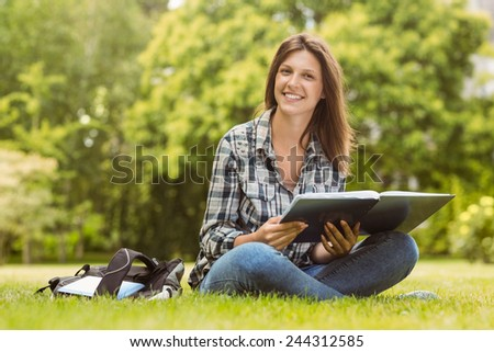 Smiling student sitting and holding a book in park at school