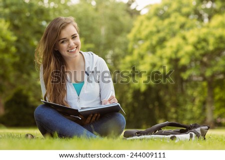 Smiling student sitting and holding book in park at school