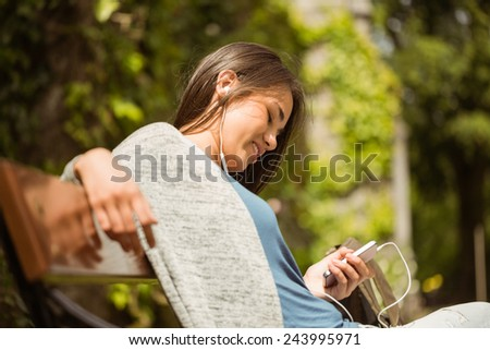 Smiling student sitting on bench text message on her mobile phone in park at school