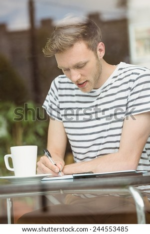 Smiling student sitting with a hot drink and writing on notepad in cafe at the university - stock photo