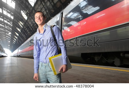 Smiling student standing on the platform of a train station - stock photo
