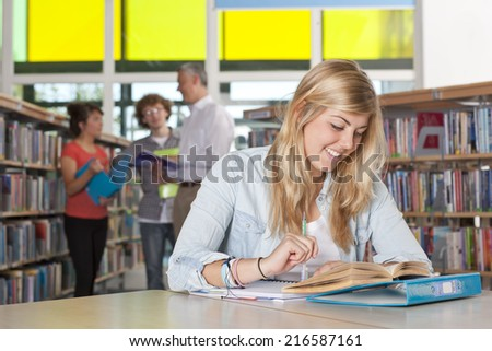 Smiling student studying in school library - stock photo