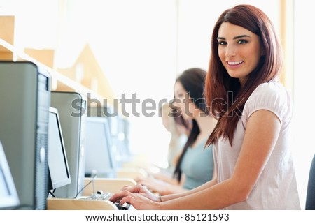 Smiling student using a computer in an IT room