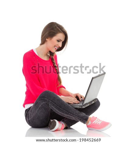 Smiling student using laptop. Happy young woman sitting with legs crossed and using laptop. Full length studio shot isolated on white. - stock photo