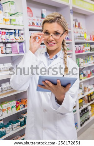 Smiling student using tablet pc in the pharmacy