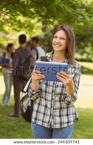 Smiling student with a shoulder bag and using tablet computer in park at school - stock photo