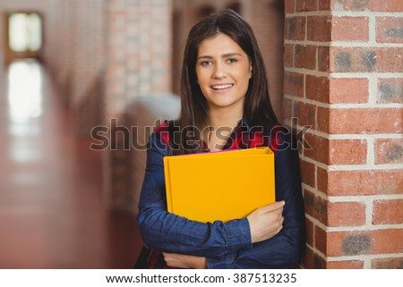 Smiling student with binder posing in the hallway - stock photo