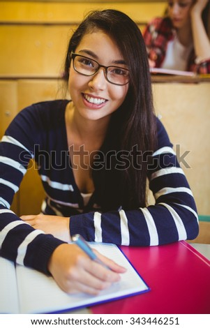 Smiling student writing on notebook at the university - stock photo