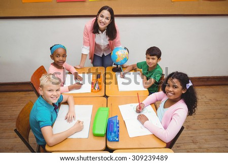 Smiling students and teacher looking at the camera at the elementary school - stock photo