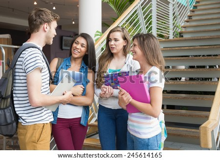 Smiling students chatting together outside at the university - stock photo