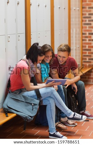 Smiling students sitting on bench using tablet in school - stock photo