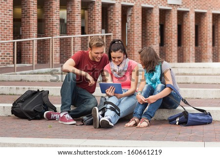 Smiling students sitting on stairs using tablet in school - stock photo