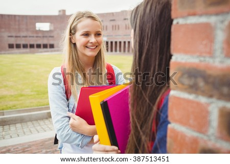 Smiling students talking outdoor at university - stock photo