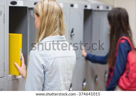 Smiling students using locker at university - stock photo