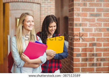 Smiling students with books in the hallway at university - stock photo