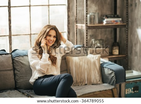Smiling stylish brunet woman in elegant clothing sitting on divan and talking smartphone in loft apartment - stock photo