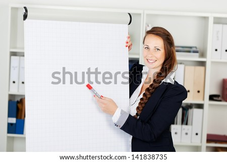 Smiling stylish business woman pointing to a blank flip chart with a red marker as she makes a presentation in an office, copyspace for your text or advertisement - stock photo