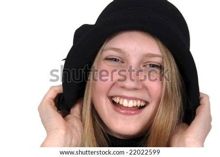 Smiling stylish teenage girl, pulling her black hat down over her ears..