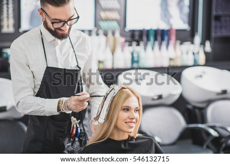 Smiling stylist is dying long hair