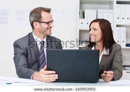 Smiling successful business colleagues in the office sitting at a desk sharing a laptop computer pausing to look at each other with satisfied smiles - stock photo