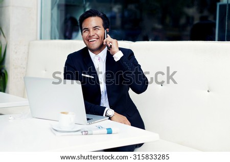 Smiling successful businessman sitting in modern expensive restaurant with open laptop and cup of coffee,wealthy happy man in a luxurious suit talking on smart phone and looking so happy and satisfied - stock photo