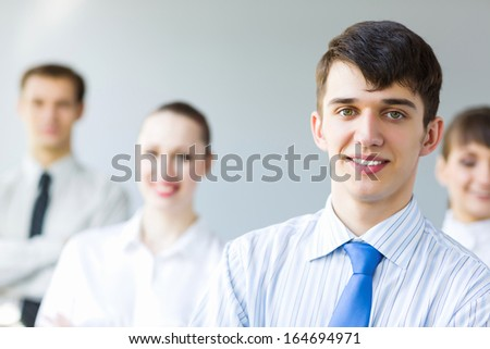 Smiling successful businessman with colleagues at background