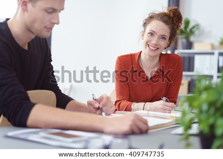Smiling successful young businesswoman sitting at a desk working with a male colleague or paper on paperwork