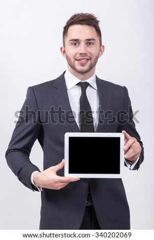 Smiling successful young student on a white background in a classic gray suit and tie presents a tablet screen with a snow-white smile. - stock photo