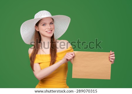 Smiling summer style woman showing blank parcel - big envelope with copy space for text looking at camera, over green background - stock photo