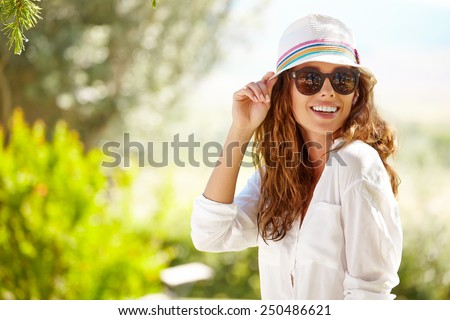 Smiling summer woman with hat and sunglasses  - stock photo