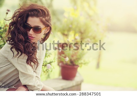 Smiling summer woman with sunglasses in italian garden - stock photo