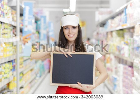 Smiling Supermarket Employee Holding a Blank Blackboard Young sales clerk in a market store with empty advertisement board  - stock photo