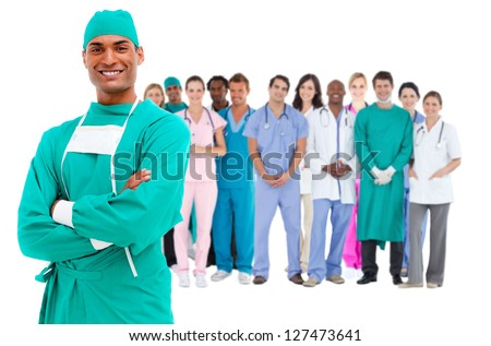 Smiling surgeon with medical staff behind him on white background - stock photo