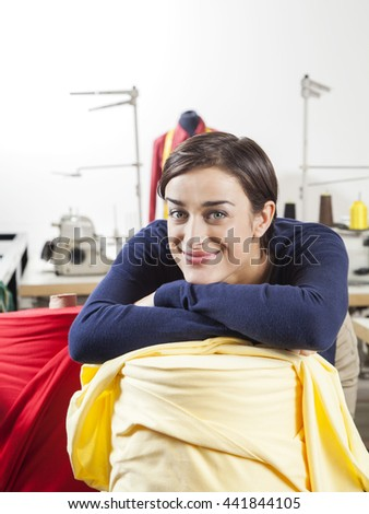 Smiling Tailor Leaning On Fabric Spool - stock photo