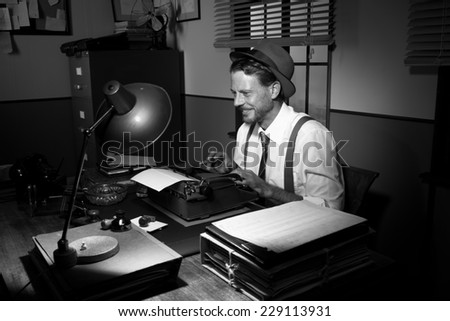 Smiling talented reporter typing on a typewriter in his office. - stock photo