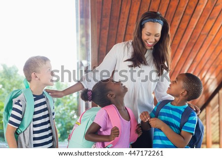 Smiling teacher and kids talking with each other at school - stock photo