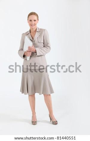 Smiling teacher holding laptop - stock photo