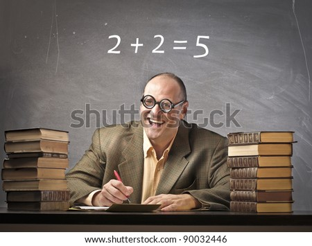 Smiling teacher in a classroom with wrong calculation on the blackboard in the background - stock photo