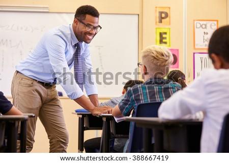 Smiling teacher leaning on elementary school pupilâ??s desk - stock photo