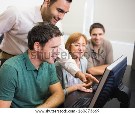 Smiling teacher showing something on screen to mature student in the computer room - stock photo