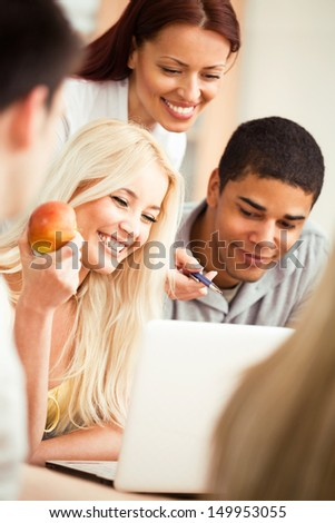 Smiling teacher showing something to her students on a laptop. - stock photo