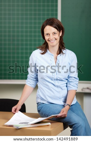 Smiling teacher sitting in the classroom and reading a book