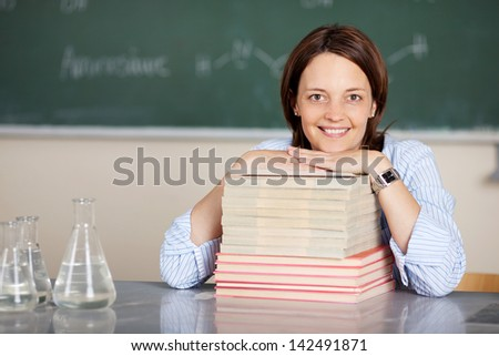Smiling teacher sitting with book stacks on the table - stock photo