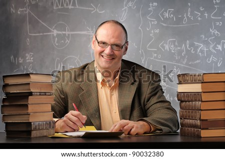Smiling teacher surrounded by books in a classroom - stock photo